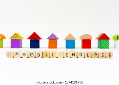 """Wooden block with letters saying """"Immobilienblase"""" (German for real estate bubble) in front of colorful toy houses"""