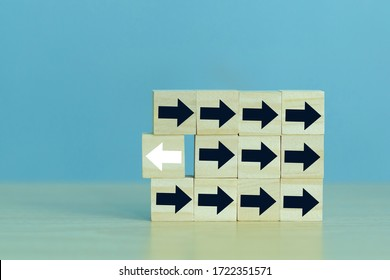 Wooden block with White arrow facing the opposite direction with black arrows, Unique, think different, individual and standing out from the crowd concept