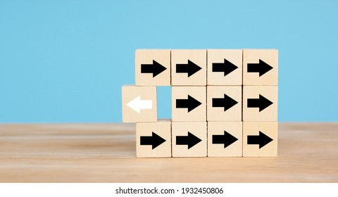 Wooden block with white arrow facing opposite direction new way, solve problem with new thinking, standing out from crown, individual, leadership concept.