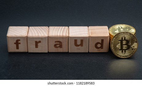 Wooden block with word FRAUD and bitcoins. Cryptocurrencies concept.