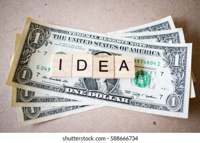 Wooden block word idea and Dollar banknote on wooden background