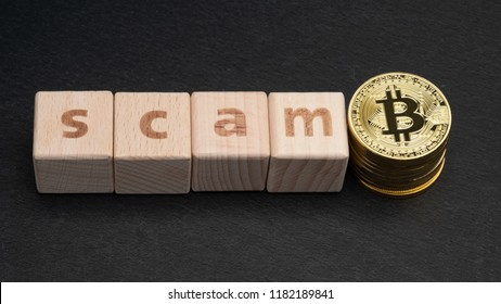 Wooden block with word SCAM and bitcoins. Cryptocurrencies concept.