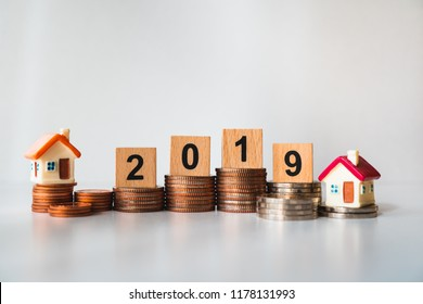 Wooden block year 2019 and mini house on stack coins using as business and financial concept