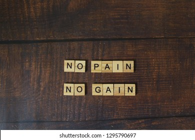 Wooden blocks arranged with the words NO PAIN NO GAIN on wooden floor