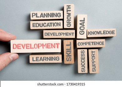 Wooden blocks with Development, Skill, Education, Learning and Planning concept related words being held by a human hand.