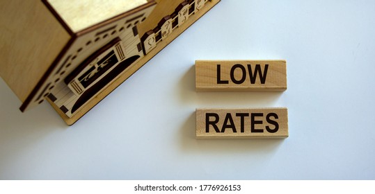 Wooden blocks form the words 'low rates' near miniature house. Beautiful white background, copy space.
