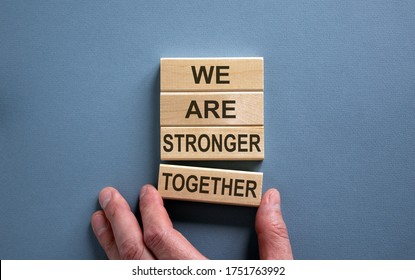 Wooden blocks form the words 'we are stronger together' on blue background. Male hand. Business concept. Copy space.