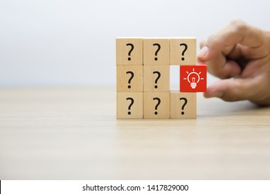 Wooden blocks with graphics, question marks and light bulbs, meaning new ideas. Thinking for change And formal leadership, ideas