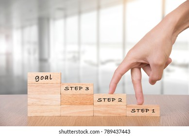 wooden blocks with hand walk go to stair to goal concept.