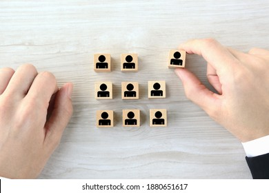 Wooden blocks with human pictogram picked out from employee group by business man's hand