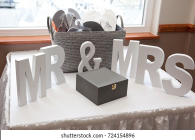Wooden blocks with letters signifying wedding or marriage, with box and sandals displayed
