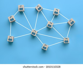 Wooden blocks with people icon interconnected by white lines on blue background. Cooperation, teamwork, business training concept. Social connections, joining to solve tasks