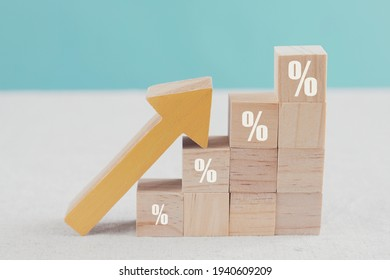 Wooden blocks with percentage sign and arrow up, financial growth, interest rate increase, inflation concept