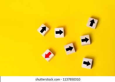 Wooden blocks with red arrow facing the opposite direction black arrows, Unique, dissenting opinion, individual and standing out from the crowd. divergent views
