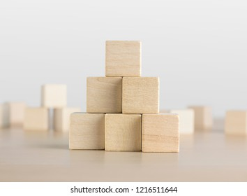 Wooden blocks stacking as a pyramid staircase on white background. Success, growth, win, victory, development or top ranking concept.