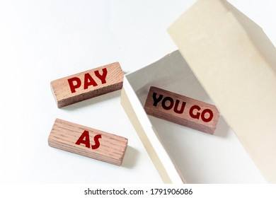 wooden blocks with text PAY AS YOU GO in a box on a white background