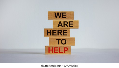 Wooden blocks with text 'we are here to help'. Beautiful white background, copy space. Business concept.