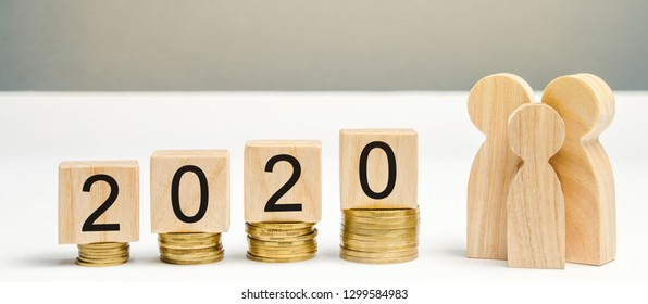 Wooden blocks with the word 2020, coins and family. Concept of saving money for the future. Budget planning for 2020. Investing. Favorable money distribution. Profit. Income. Salary. Cash
