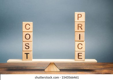 Wooden blocks with the word Cost and price on the scales. The concept of equivalence. Optimal price. A fair deal. Evaluation of goods and services, real estate and property. Fair value.