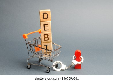 Wooden blocks with the word Debt in a supermarket trolley and a human figurine bound by handcuffs. Mandatory payment of debt. Alimony payment. Pay of a mortgage loan. Debt load / obligation. IOU