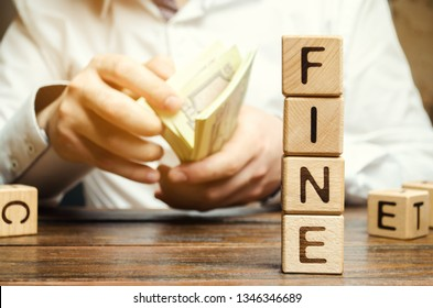 Wooden blocks with the word Fine and the man calculates the size of the fine. The concept of financial punishment. Penalty as a punishment for a crime and offense. Violations of traffic laws. Fraud.