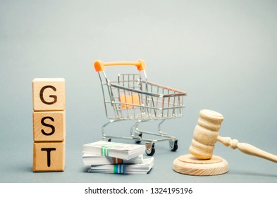 Wooden blocks with the word GST, money and a supermarket trolley with a judge's gavel. Tax, which is imposed on the sale of goods and services