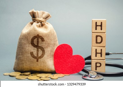 Wooden blocks with the word HDHP and money bag with dollar sign. High-deductible health plan concept. Health insurance plan with lower premiums and higher deductibles than a traditional health plan