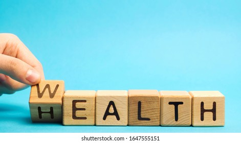 Wooden blocks with the word Health and Wealth. Concept of choosing priority in life and lifestyle. Make the right choice. Life insurance and healthcare.