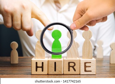 Wooden blocks with the word Hire. Headhunter selects a person from the crowd. Good choice. Human Resource Management. Recruiting Headhunting. Hiring employees. Businessman points to the green man