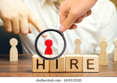 Wooden blocks with the word Hire. Headhunter selects a person from the crowd. Good choice. Human Resource Management. Recruiting Headhunting. Hiring employees. Focus on the word. Selective focus