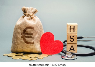 Wooden blocks with the word HSA and money bag with stethoscope. Health savings account. Health care. Health insurance. Investments. Tax-free medical expenses. Coins and euro sign. Red heart