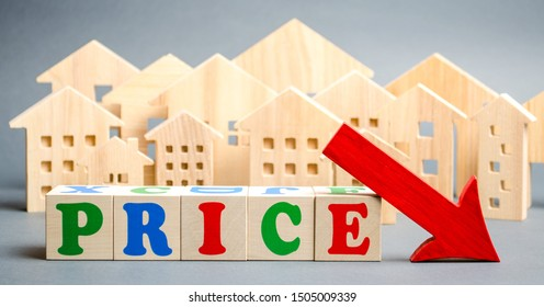 Wooden blocks with the word Price, down arrow and wooden houses. The concept of low cost real estate. Lower mortgage interest rates. Falling prices for rental housing and apartments.