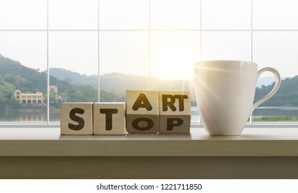 Wooden blocks with the word START-STOP and coffee on table with panoramic lake landscape background in the morning. Start, Start up, new career or new business, mindset concept.