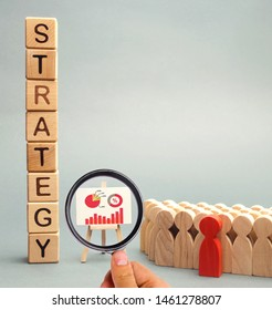 Wooden blocks with the word Strategy, business schedule and team of employees. Business strategy is an integrated model of actions designed to achieve the goals of the company. Achievement of goals