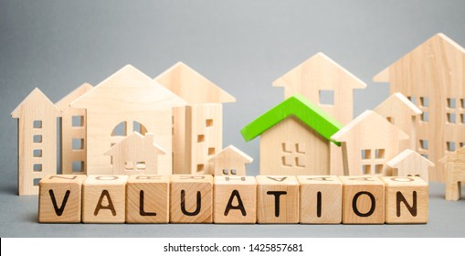 Wooden blocks with the word Valuation and many houses. Resale residential property condition. The study of the state of the house associated with the sale of housing. Property appraisal, value