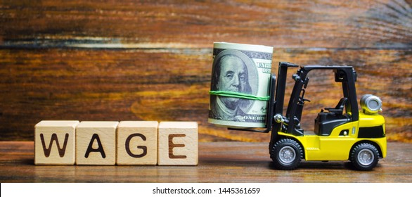 Wooden blocks with the word Wage, dollars and a forklift. Financial compensation. Salary payment to employees. Minimum and nominal wages rates. Profit and income. Business and finance