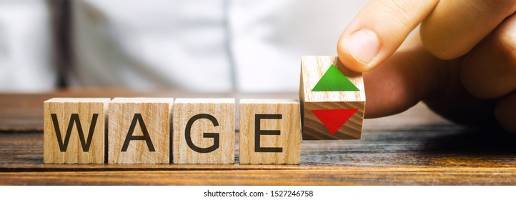 Wooden blocks with the word Wage and up and down arrows. The concept of unstable wages. Business and finance. Income, salary, revenue