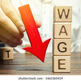 Wooden blocks with the word Wage and red arrow down. Salary reduction. Drop in profits. Financial crisis. Demote. Low profit. Capital outflow. Concept of business and finance. Recession. Businessman
