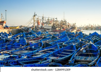 Wooden blue boats of Essaouira city harbour at sunrise in Morocco, Africa. Ocean peaceful seascape at sunset