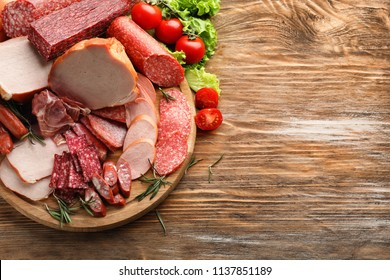 Wooden board with assortment of delicious deli meats on wooden board