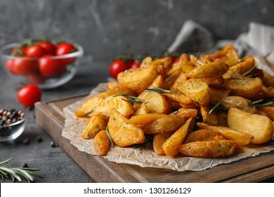 Wooden board with baked potatoes and rosemary on table