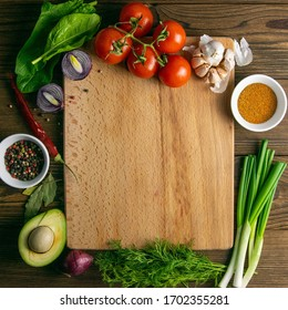 Wooden board with clear space. Around tomato and dill, olive oil, spice, peper, avocado, green onion, spinac and garlic. Top views.