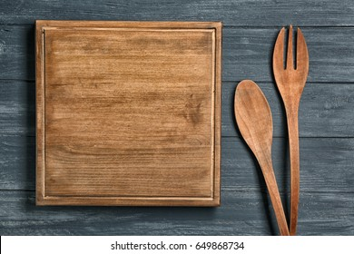 Wooden board and cooking utensils on table