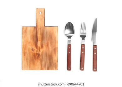 Wooden board and cutlery on white background