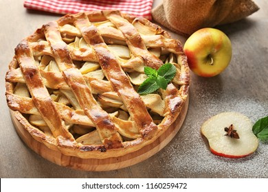 Wooden board with delicious apple pie on table