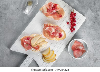 Wooden board with delicious bruschettas on table, top view