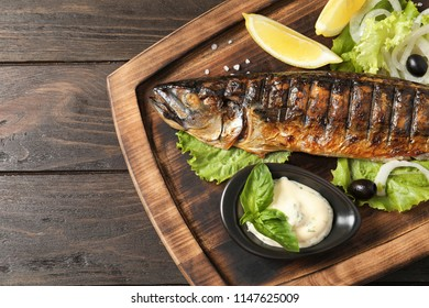 Wooden board with delicious grilled fish on table, top view