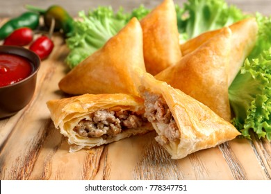 Wooden board with delicious meat samosas, closeup