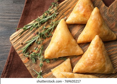 Wooden board with delicious samosas on table