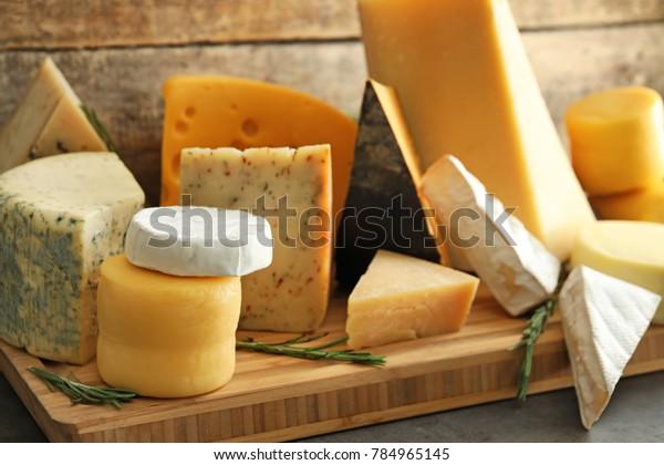 テーブルの上にいろいろなおいしいチーズを乗せた木の板